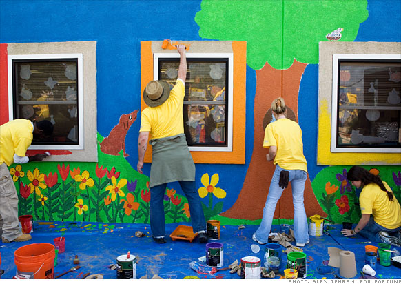 Volunteers paint a building at the Alliance For Progress Charter School in Philadelphia.