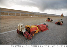 Buddhist pilgrims in prayful prostration along the railroad en route to a holy site.
